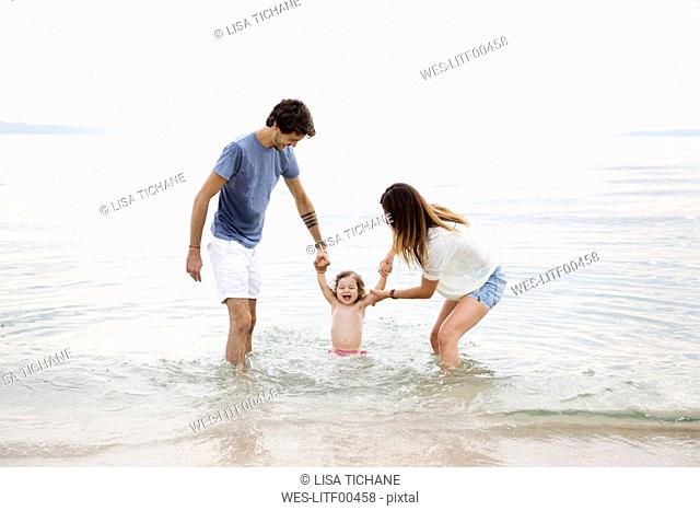 Parents playing in the sea with their little girl