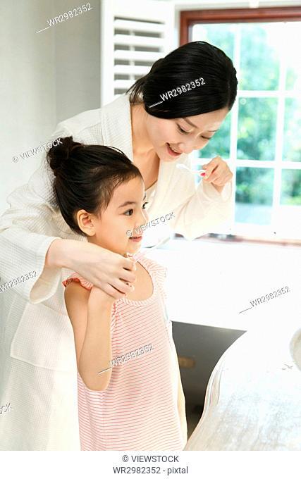 Mother teaching daughter brushing teeth
