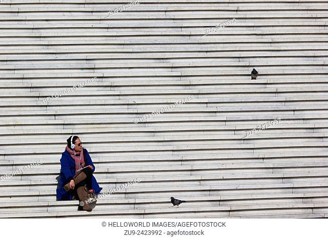 Young woman sitting on steps of the Grande Arche listening to music, La Defense, Paris, France, Europe