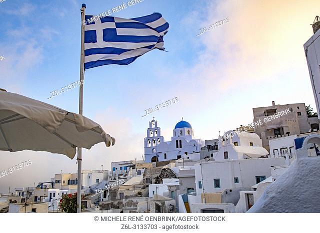 Greek flag flying in the wind of Fira, Thira, Santorini Greece