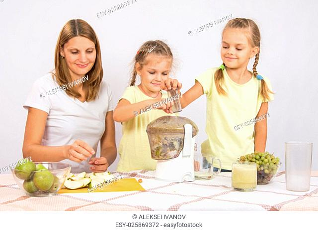 Young beautiful mother and two daughters sitting at a table squeezed juice from pears and grapes with a juicer