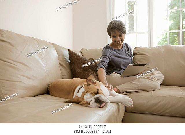 Native American woman sitting on sofa with English bulldog