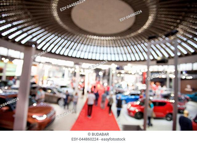 Blurred image of car exhibition show with red carpet and people walking used for background