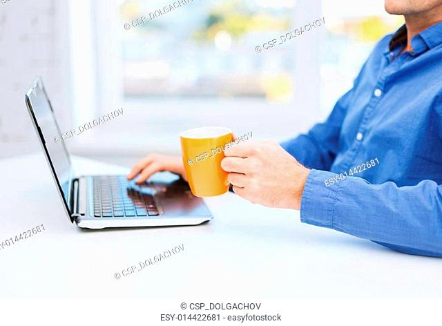 male hand with cup of tea or coffee and laptop
