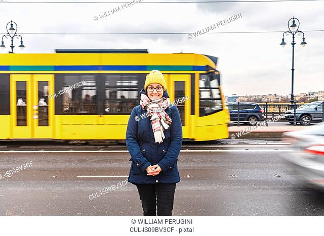 Woman posing on roadside, tram passing by in background, Budapest, Hungary