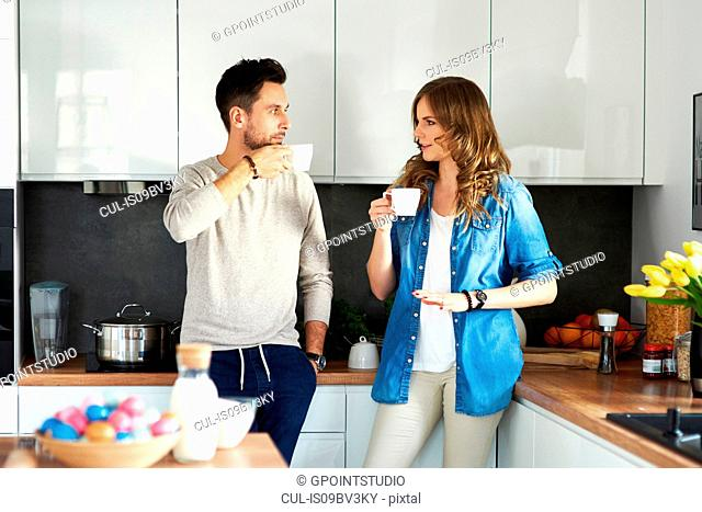 Couple drinking coffee in kitchen