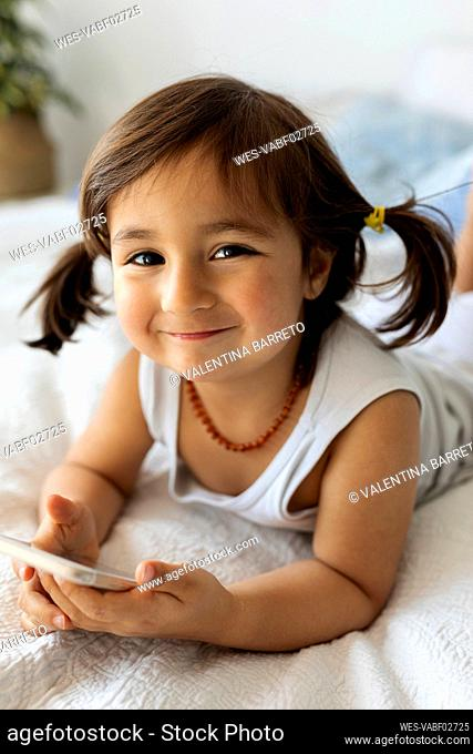 Portrait of smiling little girl with smartphone lying on bed