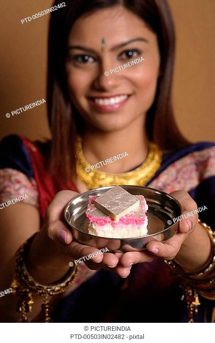 Indian woman offering plate of sweets