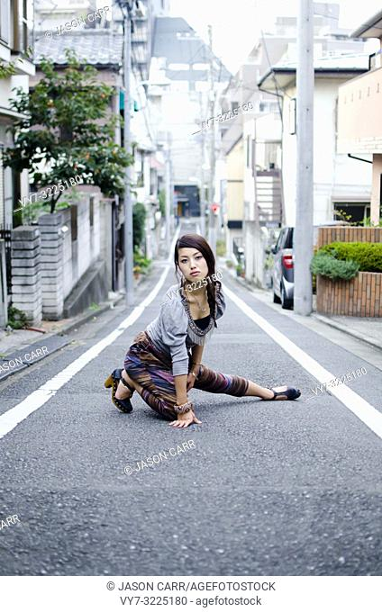 Japanese Girl poses on the street in Nakameguro, Japan. Nakameguro is a town located in the nice area of Tokyo