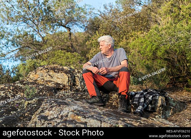 Senior man sitting on a rock in nature