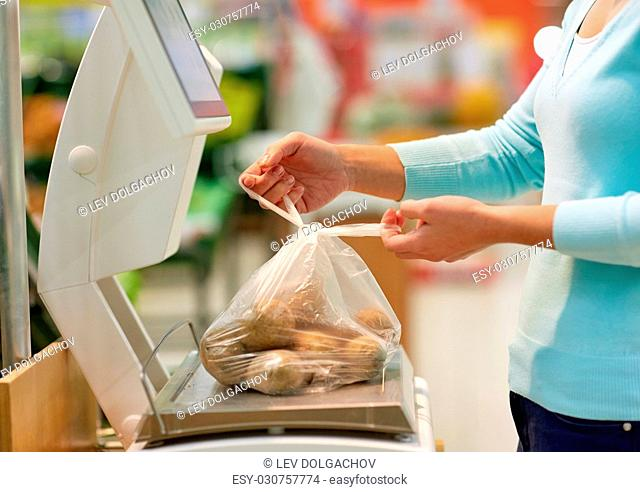 shopping, sale, consumerism and people concept - woman weighing potatoes on scale at grocery store