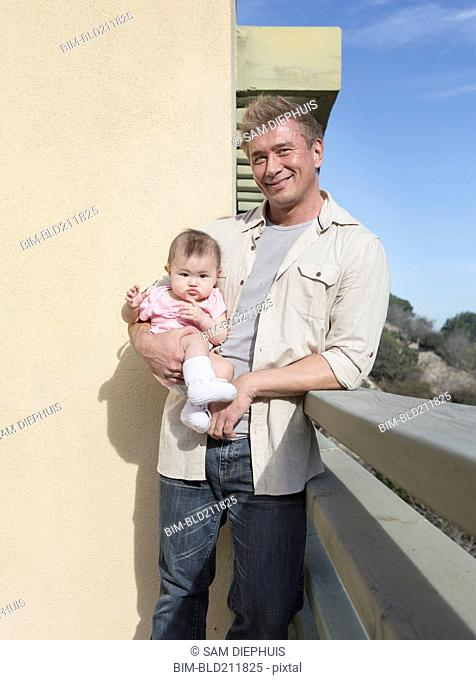 Father holding baby girl outdoors
