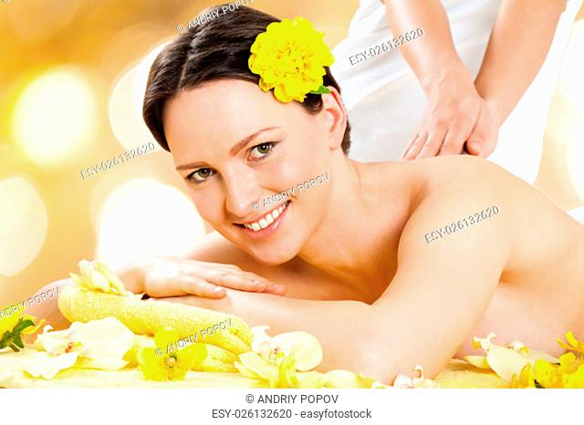 Portrait of beautiful young woman receiving back massage from massager at beauty spa