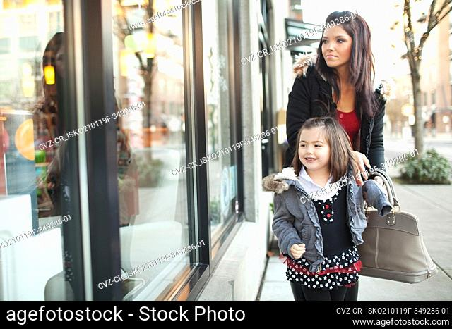 Mother and daughter window shopping in city