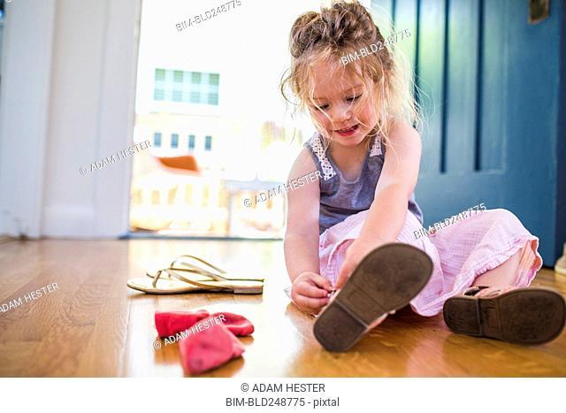 Caucasian girl sitting on floor fastening sandal