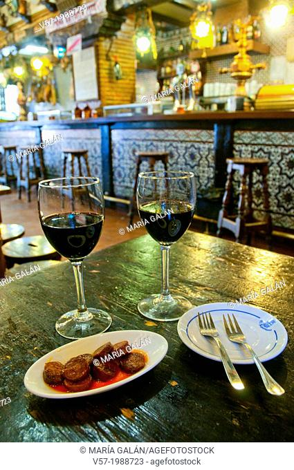 Spanish aperitif: fried chorizo with two glasses of red wine in a typical tavern. Spain