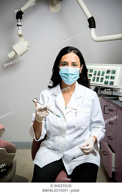 Indian dentist holding syringe in office