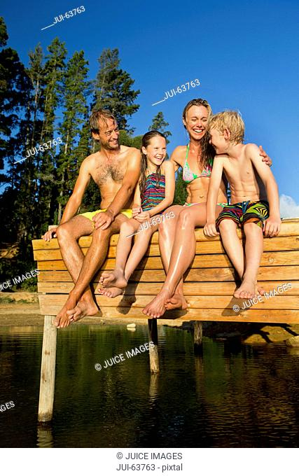 Portrait of happy family sat on jetty beside lake