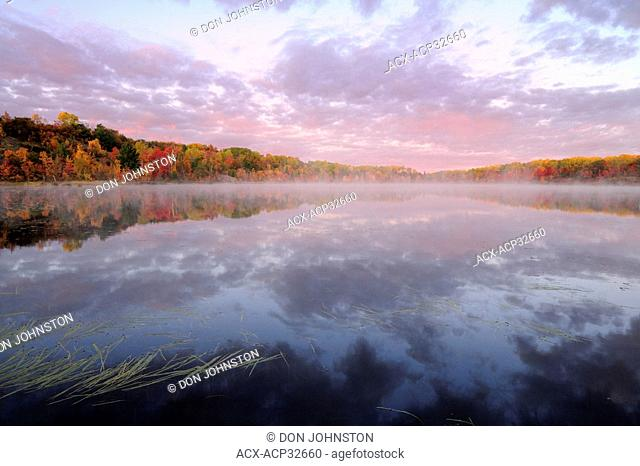 Autumn reflections in Gryphon Lake at dawn. Espanola, Ontario, Canada