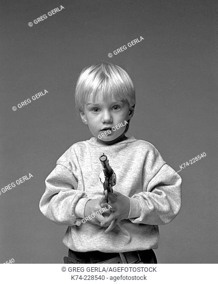 Young Boy Holding Toy Gun