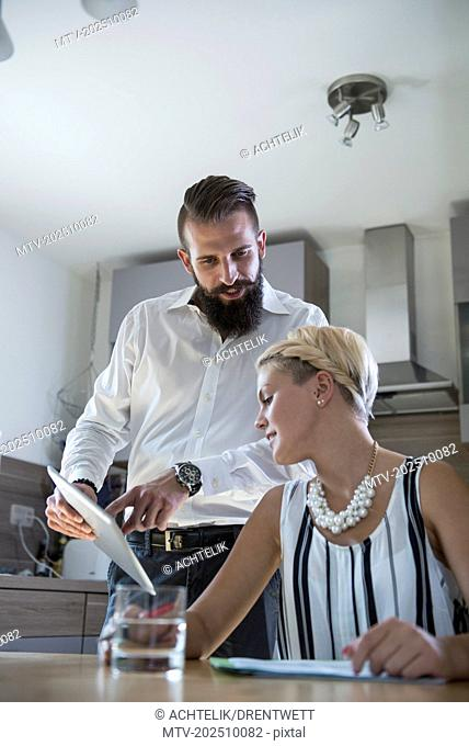 Young couple using digital tablet in the kitchen, Bavaria, Germany