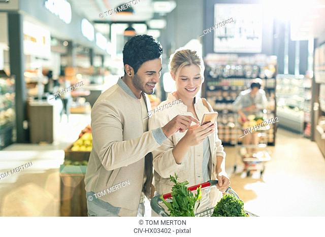 Young couple using cell phone, grocery shopping in grocery store market