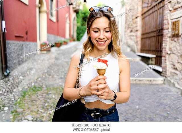 Portrait of smiling young woman with ice cream cone