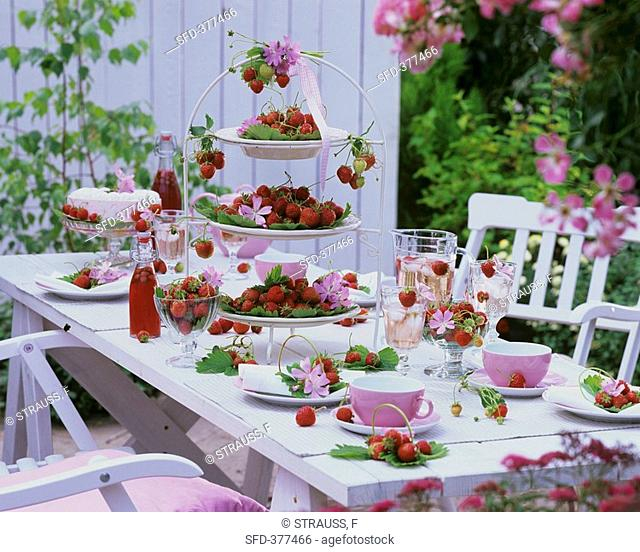 Outdoor table laid for coffee with strawberries & mallow flowers