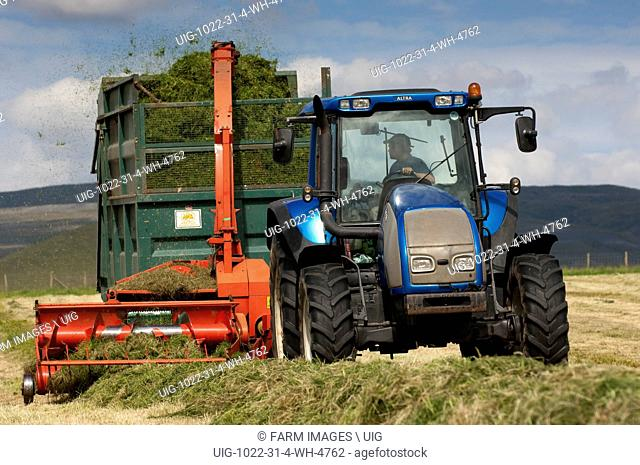 Valtra tractor pulling a Kverneland forage harvester and trailer making silage for livestock. Cumbria - England. (Photo by: Wayne Hutchinson/Farm Images/UIG)