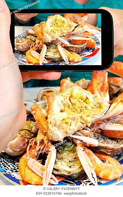 tourist photographs of plate with crab and seafood