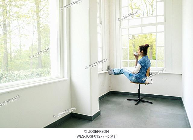 Woman with cup of coffee sitting on chair at the window