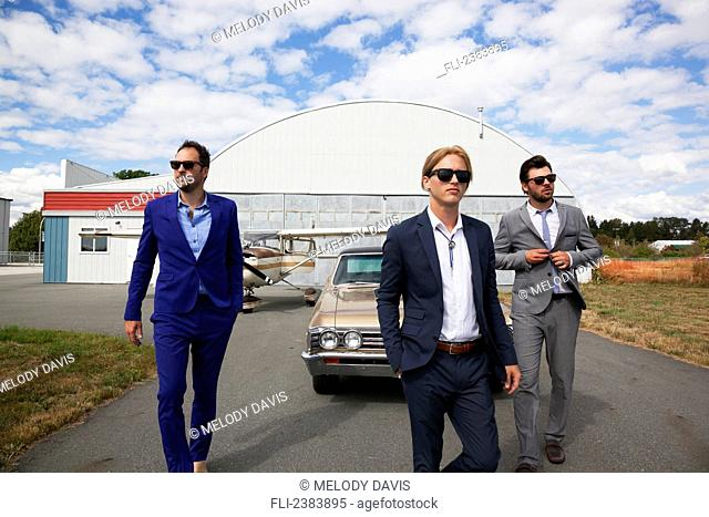 Three businessmen walking away from a car and airplane hangar; Langley, British Columbia, Canada