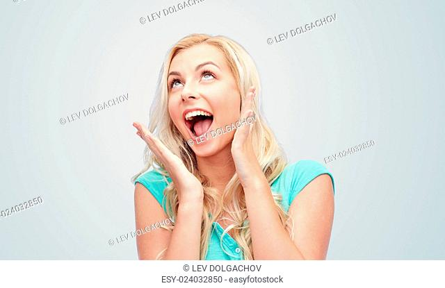 emotions, expressions and people concept - surprised smiling young woman or teenage girl over gray background