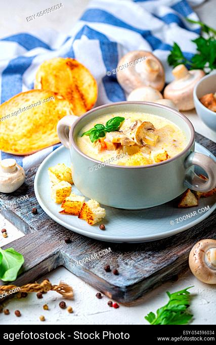 Bowl of chicken cream soup with mushrooms, croutons and green basil on a wooden serving board, selective focus