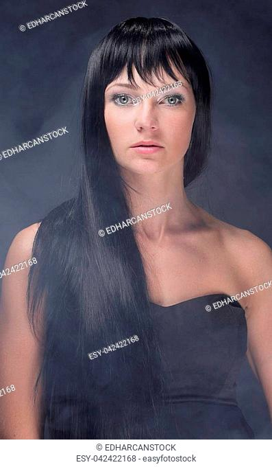 Portrait of a mystical woman with open shoulders, studio lighting a black background with smoke mist