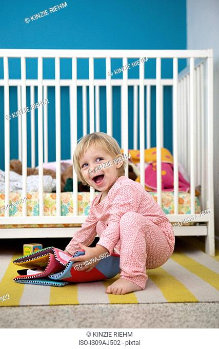 Female toddler playing with textile picture book in bedroom