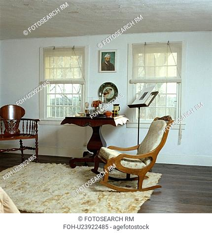 White split-cane blinds on windows in white bedroom with antique upholstered rocking chair and faux fur rug on floor