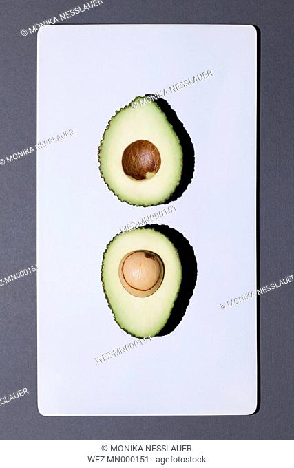 Two halves of an avocado on white board