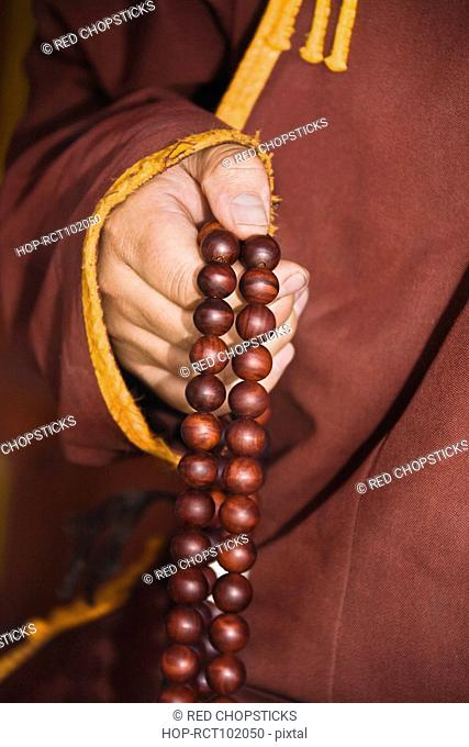 Mid section view of a monk's hand holding prayer beads, Da Zhao Temple, Hohhot, Inner Mongolia, China