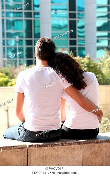 Couple sitting facing office block