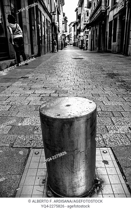 B/W image of Mayor Street of Llanes, a pile to prevent the passage of cars. Llanes, Asturias, Spain