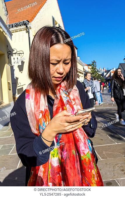 Paris, France, Chinese Tourist Shopping in Luxury Stores in La Vallee Village, Discount Shops, using Iphone on Street M.R