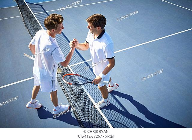 Young male tennis players handshaking at tennis net on sunny blue tennis court