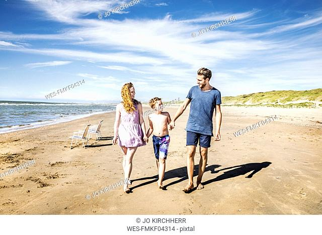 Netherlands, Zandvoort, happy family walking on the beach
