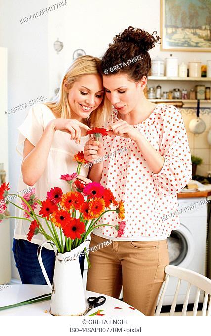 Women arranging flowers in pitcher