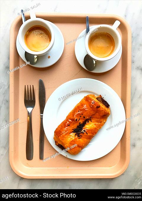 Two cups of coffee and chocolate napolitana cake on a tray. View from above