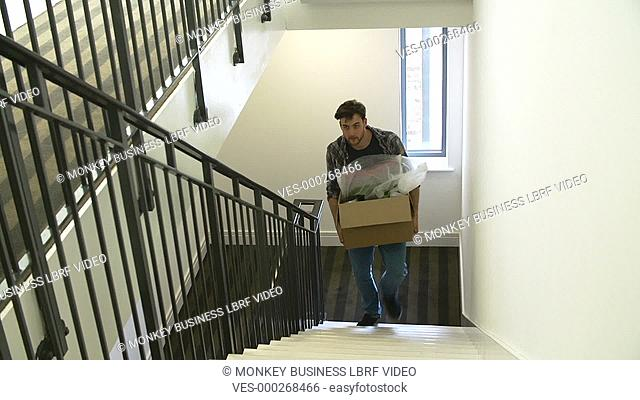 Man carrying boxes up stairs as they move into new home.Shot on Sony FS700 in PAL format at a frame rate of 25fps