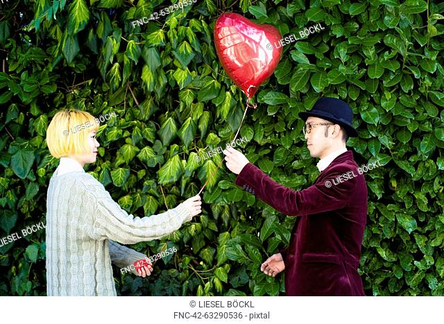Young man giving heart shape balloon to woman in park