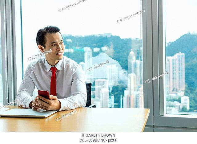 Business man at desk with smartphone looking away smiling