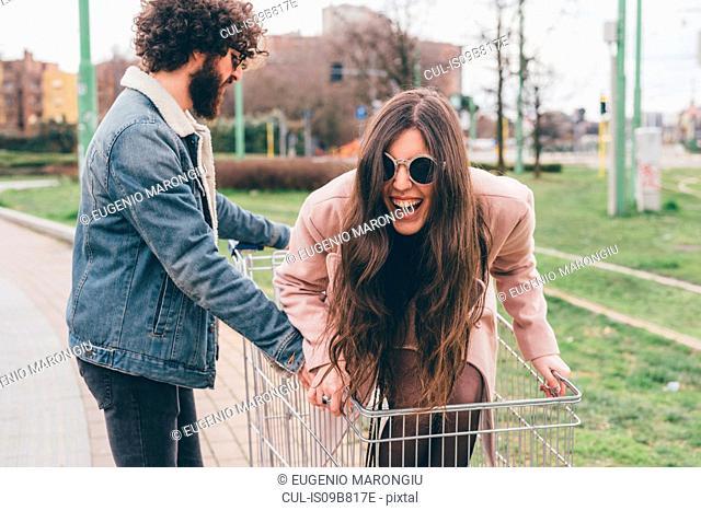 Young couple outdoors, man pushing woman along in shopping trolley